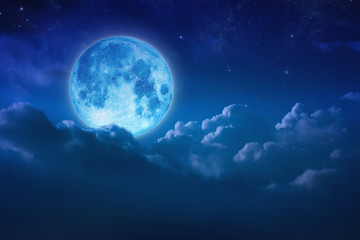 Beautiful blue moon behind cloudy on sky and star at night. Outdoors at night. Full lunar shine moonlight over cloud at nighttime with copy space background for headline text and graphic design.