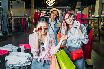 multicultural hipster girls choosing sunglasses in boutique, friends shopping concept concept
