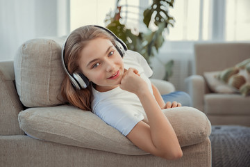 Beautiful teenage girl with smartphone and headphones listening music.