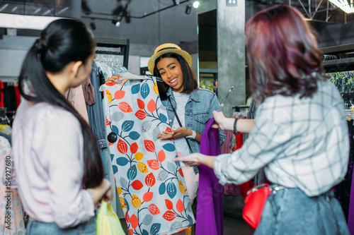 african american hipster girl with friends choosing clothes in ...