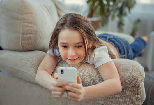 Beautiful little girl with smartphone. Leisure, children, technology and people concept
