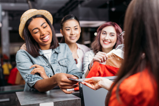 Happy stylish young women paying with credit card in shopping mall, young girls shopping concept