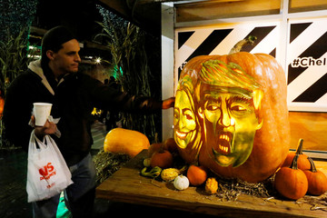 A man touches a giant pumpkin created with the faces of 2016 Democratic nominee Hillary Clinton and Republican presidential nominee Donald Trump in New York