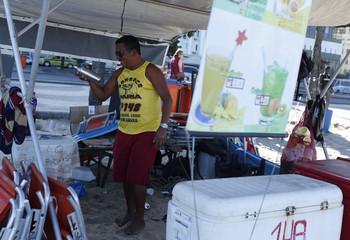 "Man prepares a ""Caipirinha"" drink at his stall at Copacabana beach in Rio de Janeiro"
