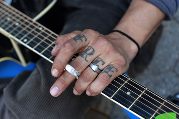 """Occupy Wall Street activist with the word """"Free"""" tattooed on his hand plays a guitar during a May Day demonstration in New York"""
