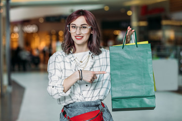 Happy young stylish woman pointing at shopping bags, boutique shopping concept