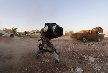 A Free Syrian Army fighter runs while holding a weapon in Wadi Al-Dayf