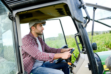 handsome young male farmer driving his tractor during harvest in the field countryside