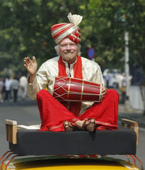 Virgin Group founder Richard Branson plays a dhol, an Indian musical instrument, while sitting atop a taxi during a promotional event in Mumbai