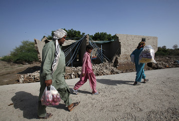 Villagers, displaced by flooding, carry their supplies as they walk past a damaged house while returning to their flooded village in Dadu