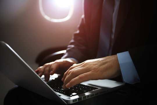 businessman with notebook sitting inside an airplane