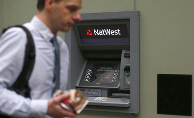 A man walks past a cash machine outside a NatWest bank in London