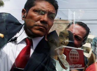 Peruvian presidential candidate Keiko Fujimori sits inside a car as security personnel are seen reflected in the windows outside a polling station in Lima