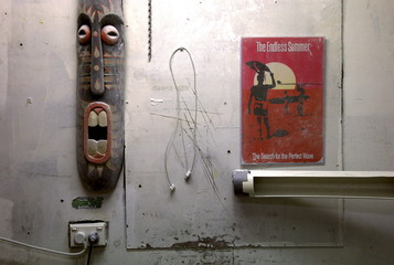 Surfing movie poster, a phone cable and a wood carving adorn the wall of a surfboard workshop owned by Craig 'Buddha' Cummins where he installs shark repellent devices in Sydney, Australia
