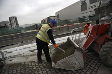 A construction worker shovels sand from teh bucket of an excavator in the Capital Dock area of Dublin