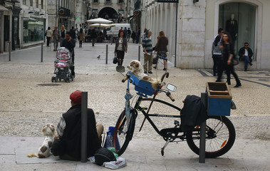 A street singer, accompanied by his dogs, rests along the shopping street Rua Augusta in downtown Lisbon