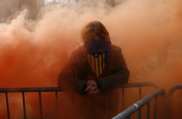 A pro-independence protestor stands surrounded by red smoke coming from a firemen protest in front of Catalonia's regional parliament as lawmakers voted inside, in Barcelona