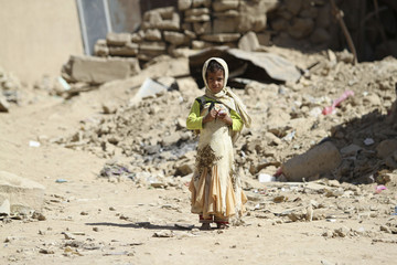 A girl stands near a house damaged during recent fighting between government forces and rebels in Saada