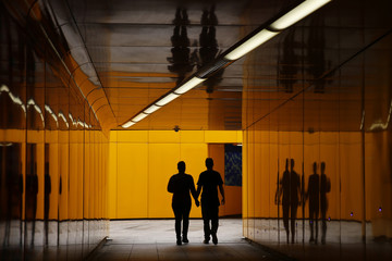 A couple are silhouetted in an underpass in London,
