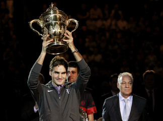 Federer holds the winner's trophy after defeating Djokovic in the final of the Swiss Indoors tennis tournament in Basel