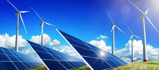 Solar panels and wind turbines on open field, with nice blue sky, white clouds and the reflection of the sun