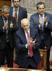 Greece's Prime Minister George Papandreou and lawmakers applaud after winning a vote of confidence during a parliament session in Athens