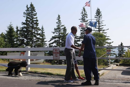 U.S. President Obama meets with U.S. Coast Guard Commander Chase as his dog 'Bo' walks behind at Bass Harbor Head Lighthouse