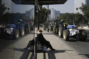 A farmer sits near a tractor with a picture of one of the 43 missing trainee teachers before a protest in Mexico City