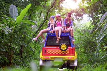 woman in group are enjoy traveling by sitting on the rack-roof of the convertible car off-road in jungle