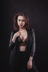 Seductive brunette model in leather jacket and black lace bra