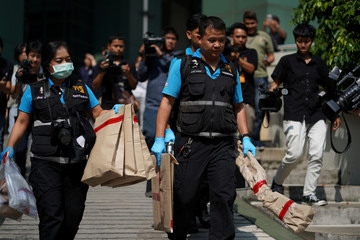 Thai forensic police carry evidence as they leave from a site of bomb blast at the Phramongkutklao Hospital in Bangkok