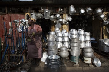 A woman stands by a local shop that sells dishes and other utensils made from recycled metal cut from oil barrels in Kamukunji, Nairobi