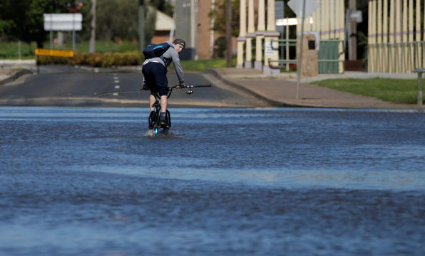 A cyclist pedals across a road flooded by the overflowing Lachlan River after a natural disaster zone was declared in the midwestern New South Wales town of Forbes