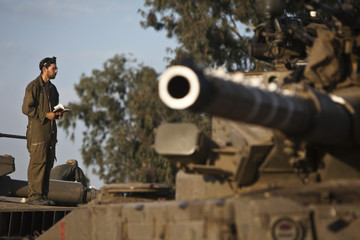 Israeli soldier prays atop a tank near the border with the central Gaza Strip