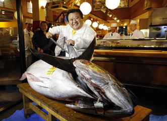 Kiyomura Co's President Kimura, who runs a chain of sushi restaurants, poses with a bluefin tuna in front of his sushi restaurant outside Tsukiji fish market in Tokyo