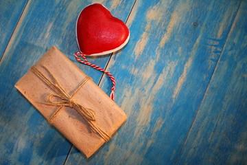 красное сердце и  подарок на синих деревянных досках