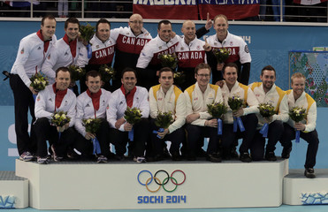 Winners from Canada pose with second-placed British team and third-placed Swedish team on podium during flower ceremony after men's curling gold medal game at 2014 Sochi Winter Olympics