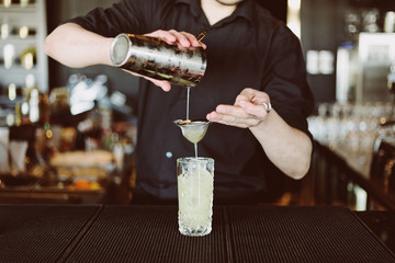 Barman's hands in bar interior making non-alcohol cocktail