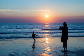 Silhouettes of mother and child enjoying the sunset on the atlantic ocean, Lacanau France