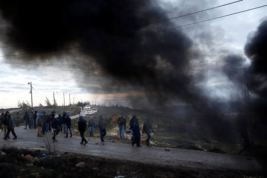 Protesters are seen next to smoke from burning tyres at the entrance to the Israeli settler outpost of Amona in the occupied West Bank