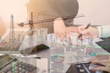 Double exposure business worker with graph finance and factory construction on desk office. concept plan investment.