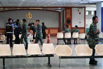 Thai military personnel and forensic experts stand near the site of the bomb blast inside Phramongkutklao Hospital in Bangkok