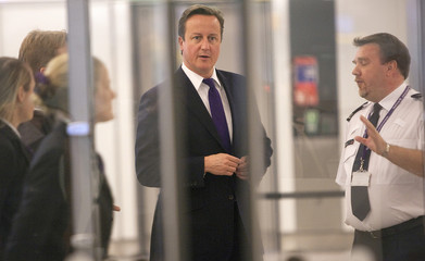 Britain's Prime Minister David Cameron watches passengers pass through immigration control during a visit to Terminal 5, at Heathrow Airport, west of London