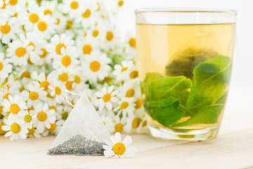Chamomile tea brewed in a glass, flowers on a background