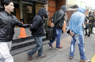 Men in handcuffs who were detained on suspicion of drug trafficking, are escorted by police outside the anti-drug unit of the National Police of Peru in Lima