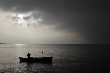 A fisherman lifts nets on Lake Leman in Lutry