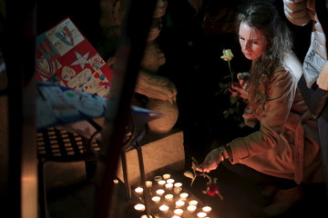 A French national lays a rose during a memorial tribute to the victims of Friday's attacks in Paris, at the French Shanghai Consulate in Shanghai
