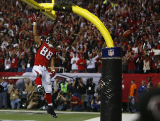 Atlanta Falcons' Gonzalez spikes the football over the crossbar as he celebrates a second quarter touchdown catch against the San Francisco 49ers in the NFL NFC Championship football game in Atlanta