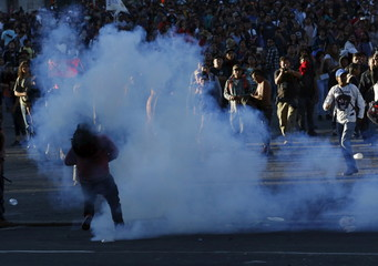 A protester stands near tear gas during clashes with riot police at a march marking the 47th anniversary of the 1968 Tlatelolco square massacre in Mexico City