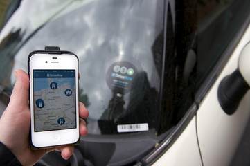 Picture illustration shows a smartphone displaying the DriveNow app with a map of Germany held up next to a car from the DriveNow service in Berlin
